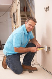 Man carrying out Small Electrical Works - installing a wall socket